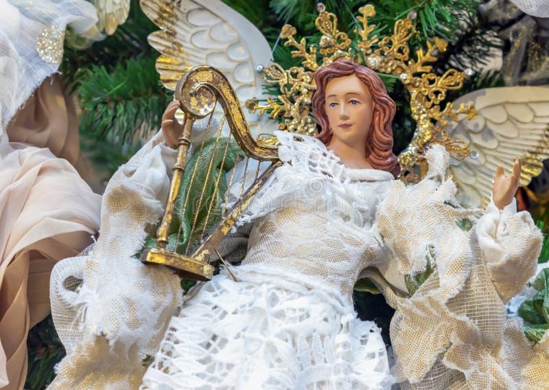 一个天使女孩的小雕象一件白色透雕细工礼服的在圣诞树 免版税库存照片