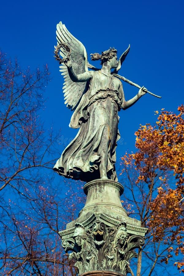一个天使的雕象在一个专栏的在明媚的阳光下 免版税库存图片