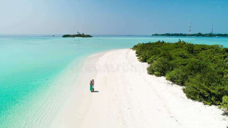 一个夫妇身分的空中射击在一个干净的沙滩的由有透明的大海的海 免版税库存照片