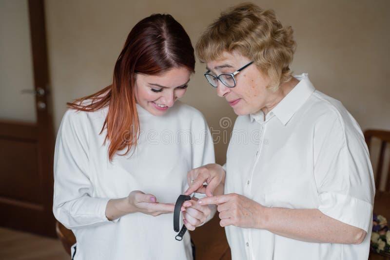 一个女人帮老妈戴上健身手镯 一个成年女儿帮妈妈整理出 免版税库存图片