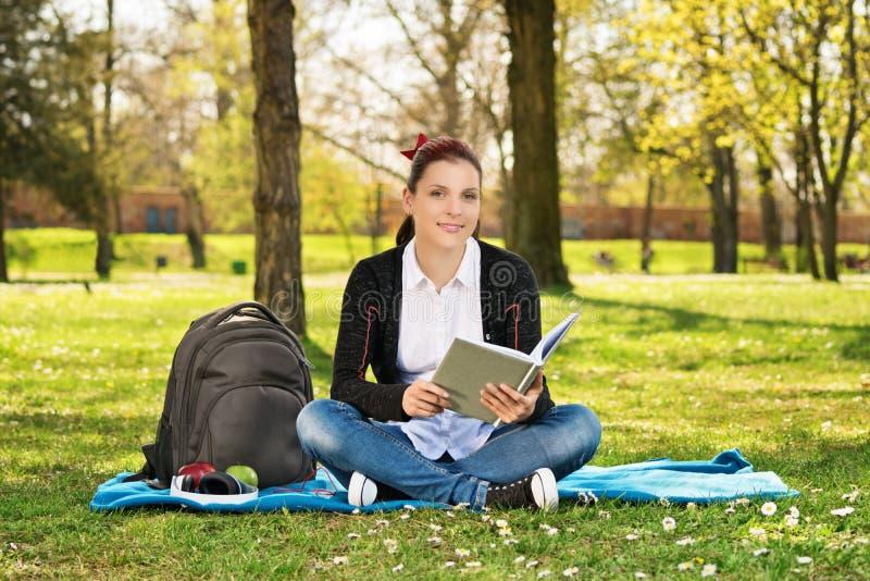 一个女学生的画象在拿着书的公园 库存图片