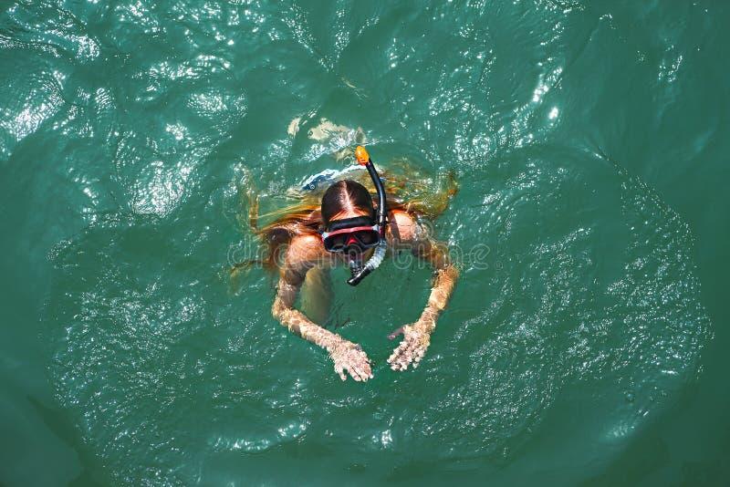 一个女孩佩带的游泳面具的空中下来上面视图在海 库存图片