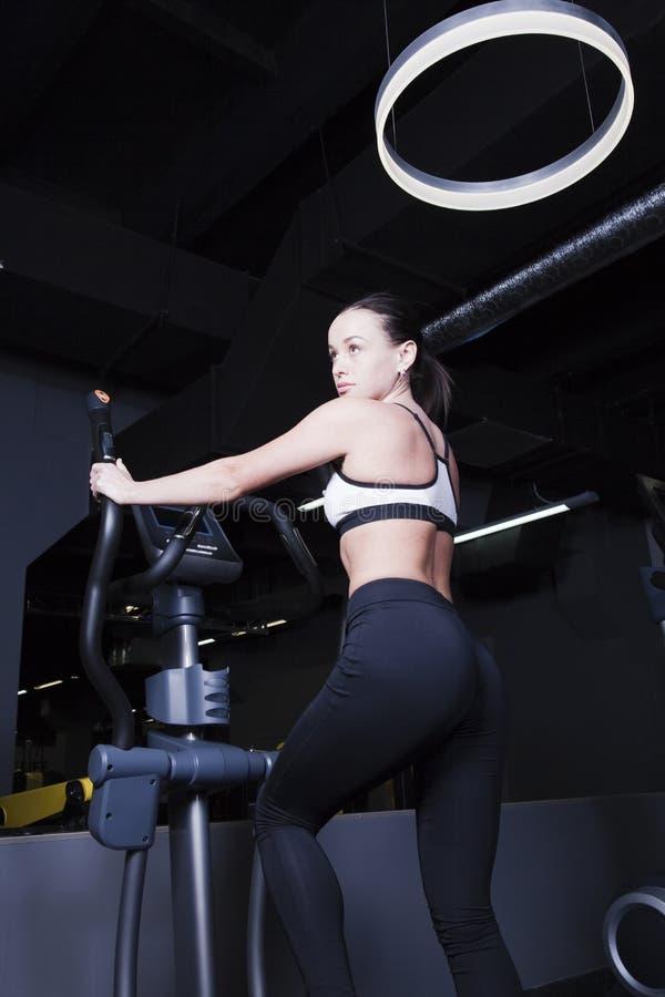 一个女孩向在健身房的体育求助 免版税库存图片