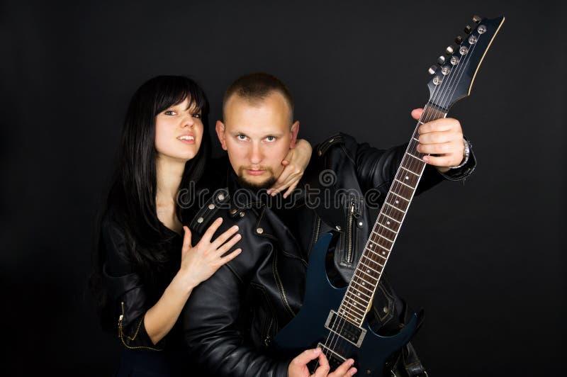 一个女孩和一个人有吉他的 免版税图库摄影
