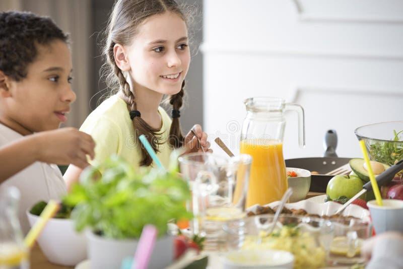 一个女孩和一个男孩由充分桌健康自创食物和fr 免版税库存照片