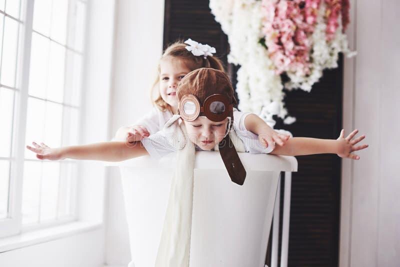 一个女孩和一个男孩的画象使用在卫生间里的试验帽子的在飞行员或水手 旅行,童年的概念和 免版税库存图片