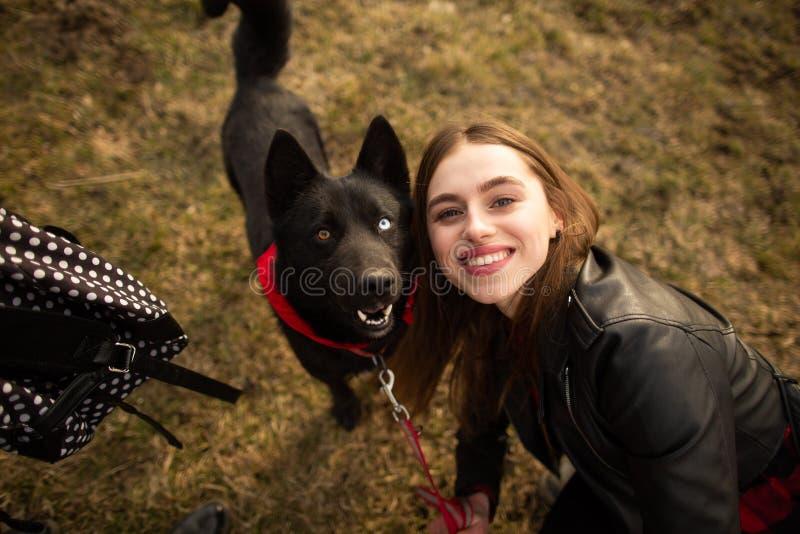 一个女孩和她的狗的一张美妙的画象与五颜六色的眼睛 朋友在湖的岸摆在 免版税库存照片