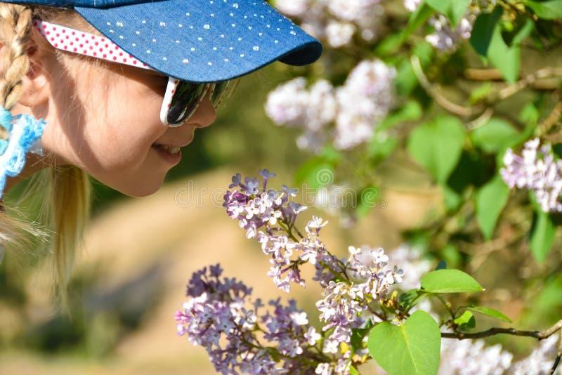 一个女孩在公园嗅到在树的淡紫色花 过敏花粉 免版税库存照片
