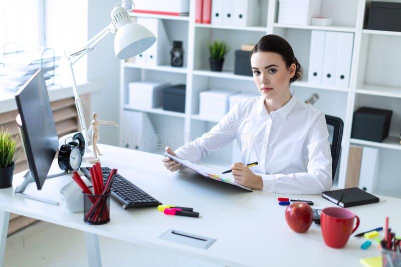 一个女孩在办公室在她的手上坐,拿着一支笔并且通过文件看 免版税库存图片