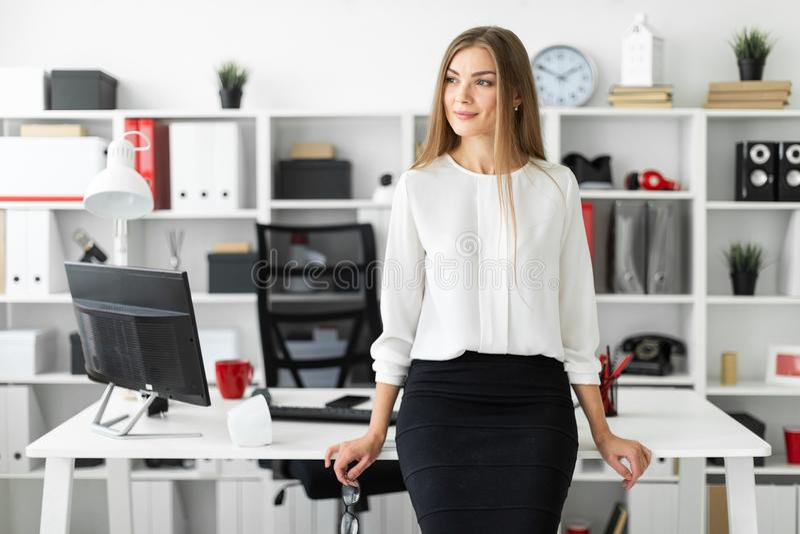 一个女孩在办公室在她的手上站立倾斜在一张桌和拿着玻璃 免版税库存照片