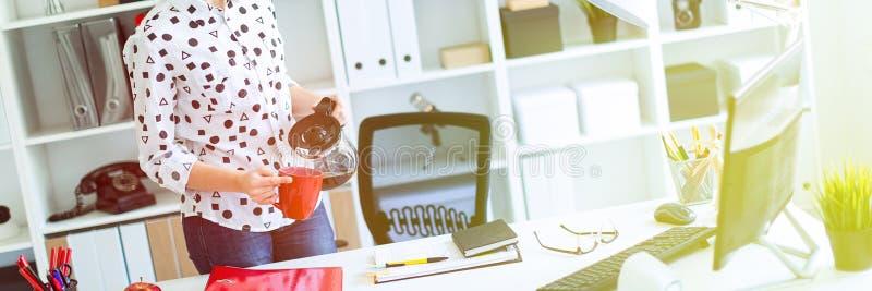 一个女孩在办公室站立在桌附近并且倒从咖啡罐的咖啡入一个红色杯子 免版税库存照片