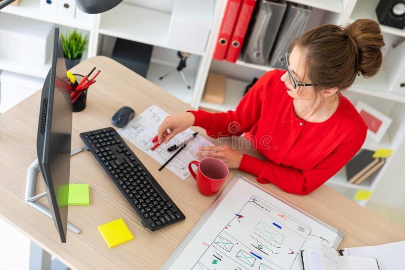 一个女孩在她的手上坐在一张桌上在办公室并且采取一支铅笔 一个磁性委员会在女孩前说谎 免版税库存照片
