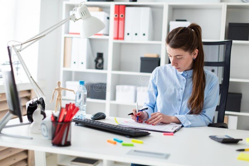 一个女孩在她的手上坐在一张桌上在办公室,拿着一支笔和与文献一起使用 免版税库存图片