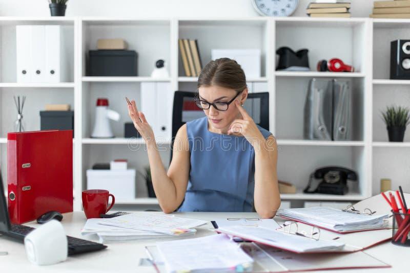 一个女孩在她的手上坐在书桌在办公室,拿着一支笔和与文件一起使用 库存图片