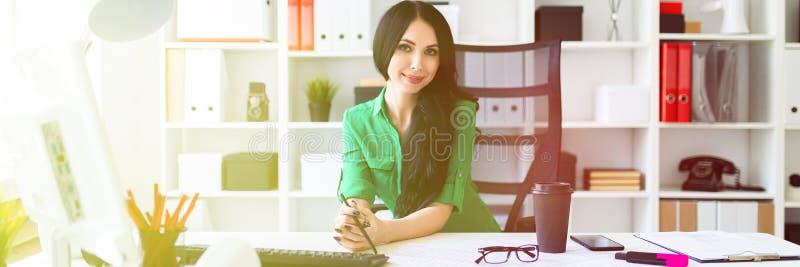 一个女孩在她的手上坐在办公室桌上并且拿着一支铅笔 库存图片