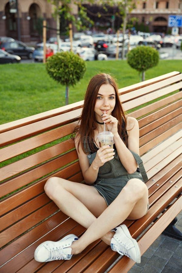 一个女孩在她的ha坐一条长凳在城市,有一份饮料的 免版税库存图片