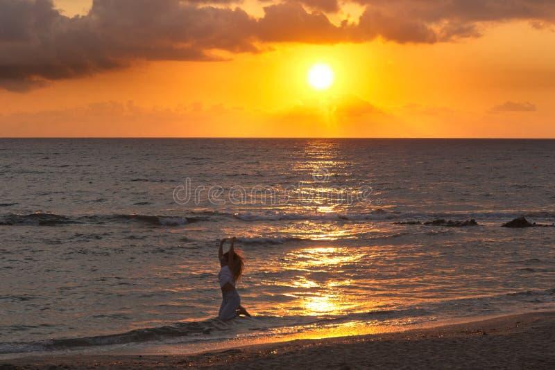 一个女孩在日出时跳到岸边,日落在西班牙安达卢西亚阿尔梅里亚的Islote del Moro 库存图片