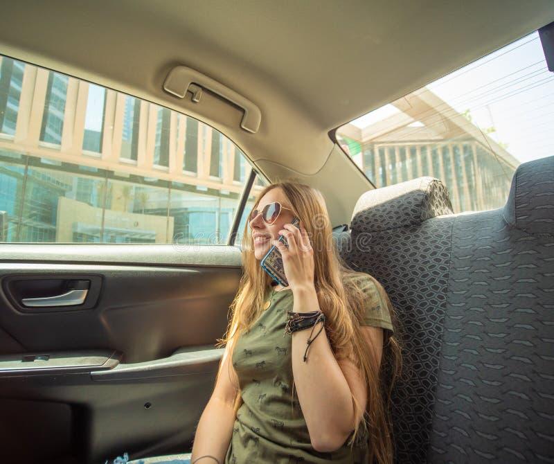 一个女孩在汽车的后座在电话坐和谈话 免版税库存图片