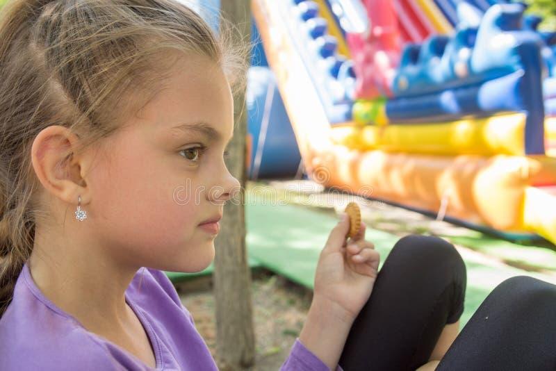 一个女孩在绷床公园咬住在长凳的肝脏 免版税库存照片