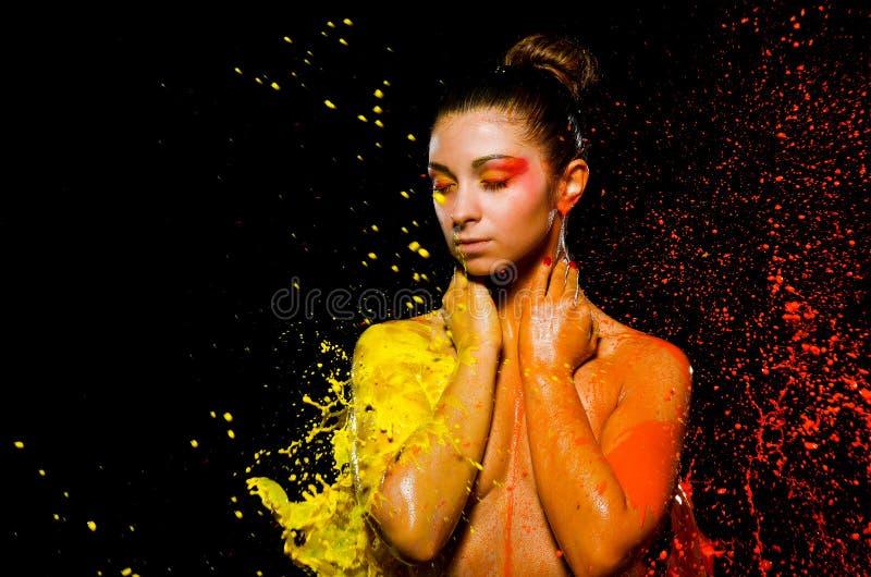 一个女孩在黄色和橙色油漆沐浴 库存图片