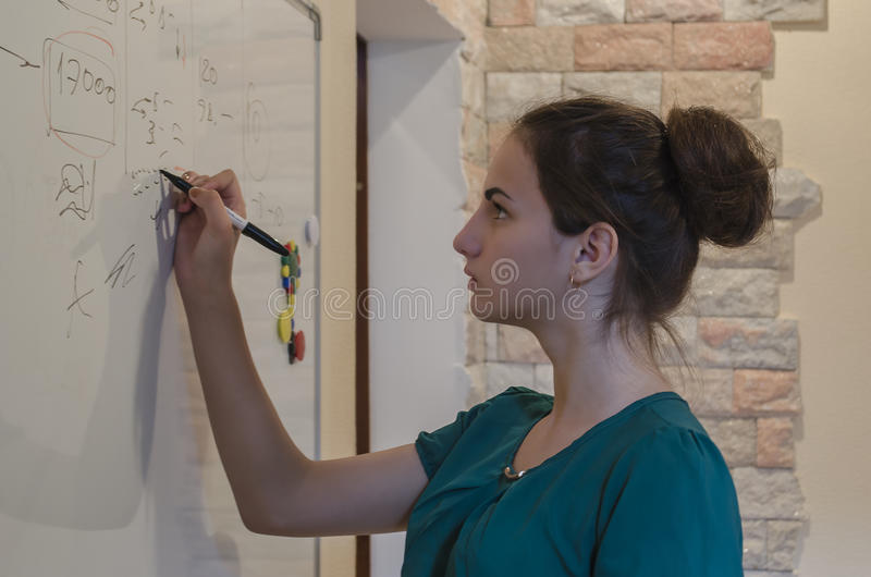 一个女孩在黑板写 免版税库存图片