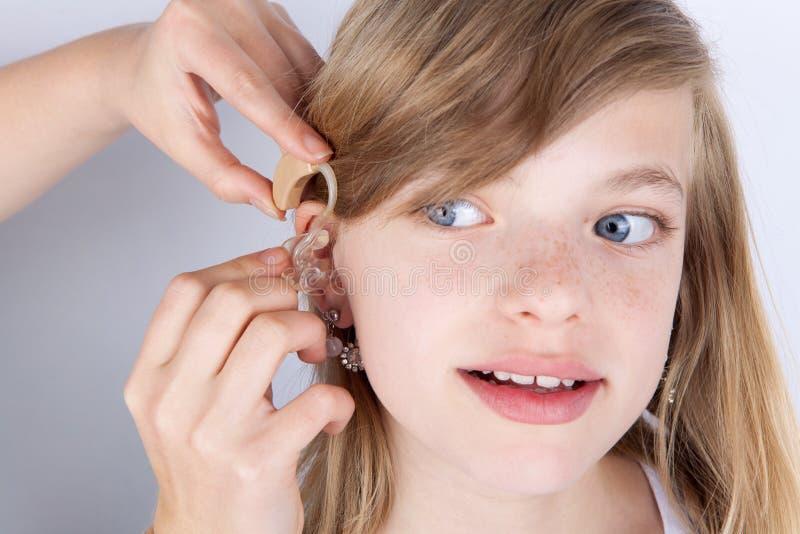 一个女孩尝试的助听器的画象 免版税库存图片