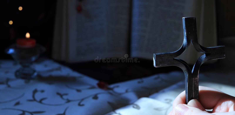 一个女孩或男孩在手上拿着一个十字架并且在晚上祈祷 背景是一本开放老圣经书和附近是蜡烛机智 库存图片