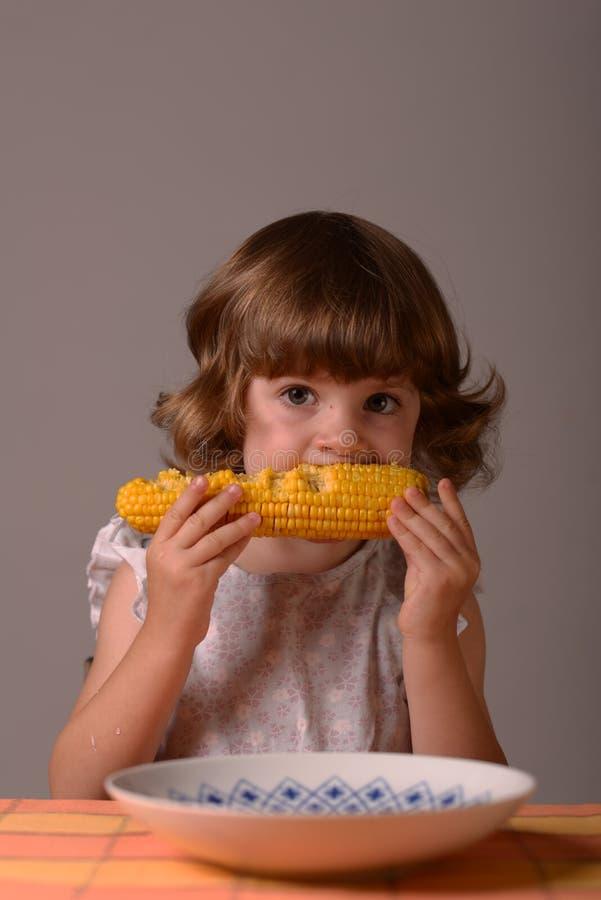 一个女孩用玉米 库存图片