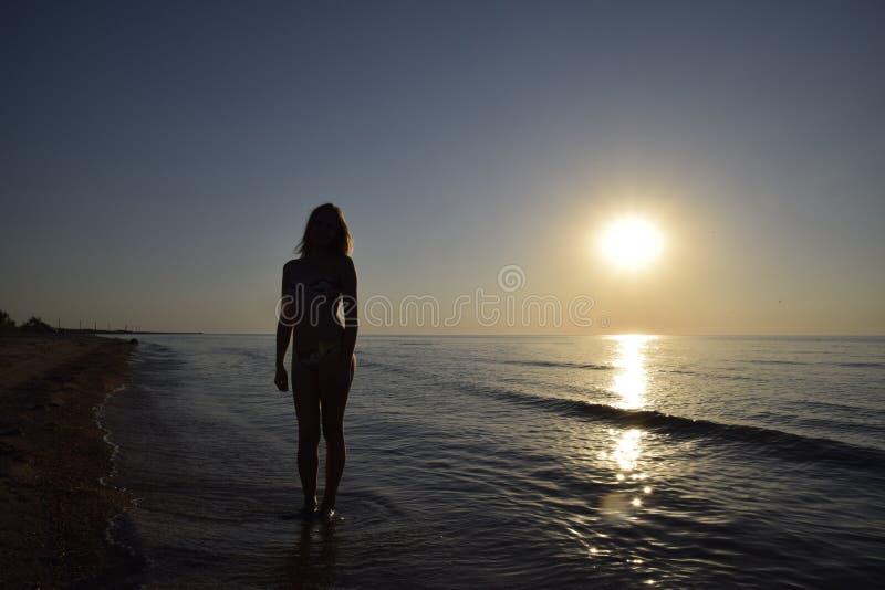 一个女孩的剪影反对日落的由海 图库摄影