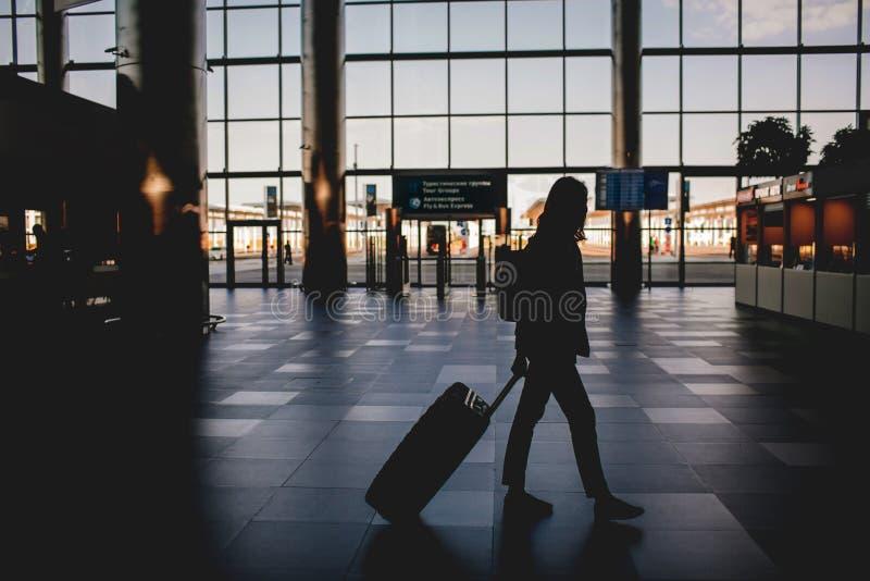 一个女孩的剪影在有手提箱和背包的机场 免版税图库摄影