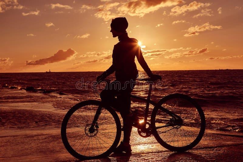 一个女孩的剪影有一辆自行车的在日落背景的沿海 库存照片