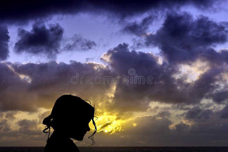 一个女孩的剪影有日出的在海洋在背景中 免版税库存照片
