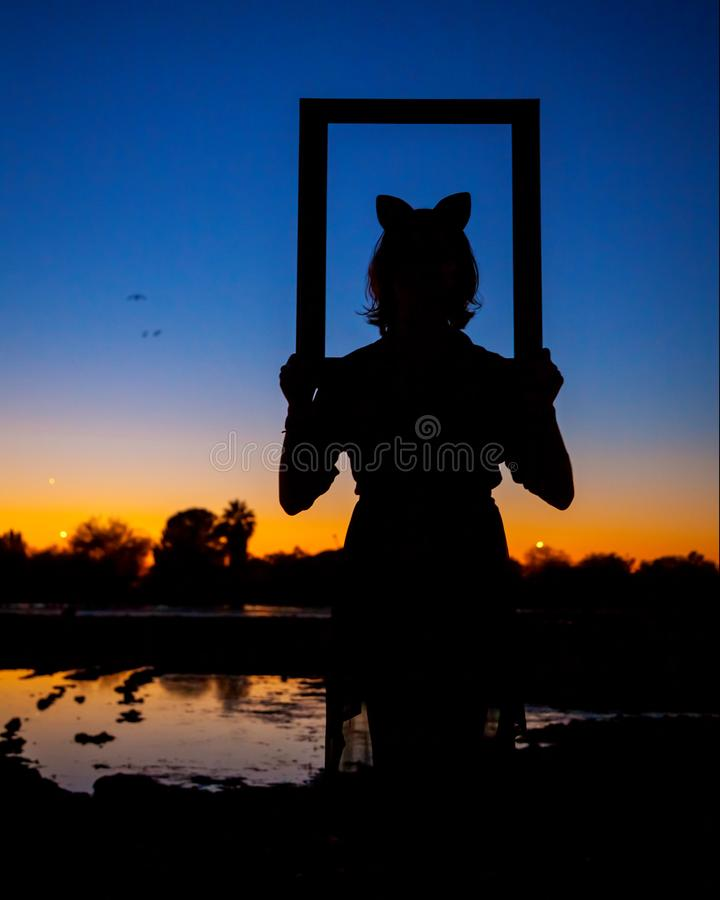 一个女孩的剪影有看通过图片Fr的猫耳朵的 库存图片