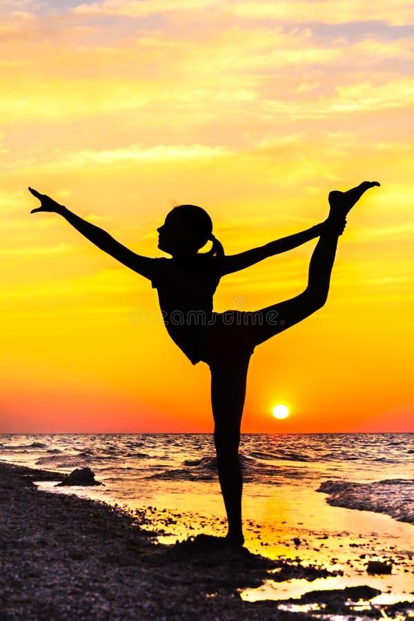 一个女孩的剪影瑜伽姿势的在日落的海滩 免版税库存照片