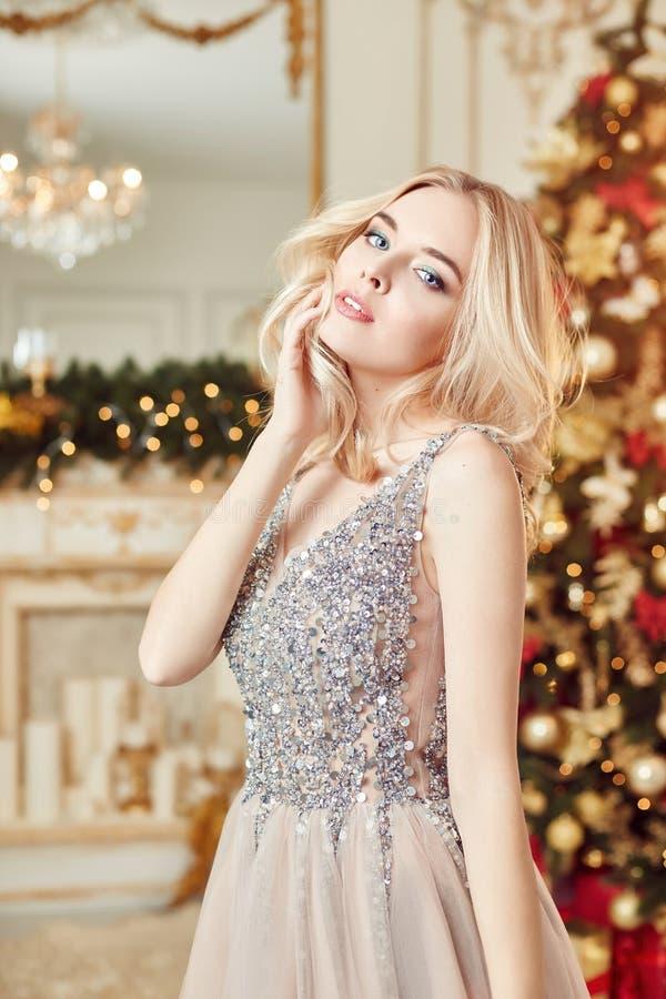 一个女孩的圣诞节画象一件闪烁的欢乐礼服的在圣诞节装饰背景在典雅的内部的 回到发型她的妇女 库存图片
