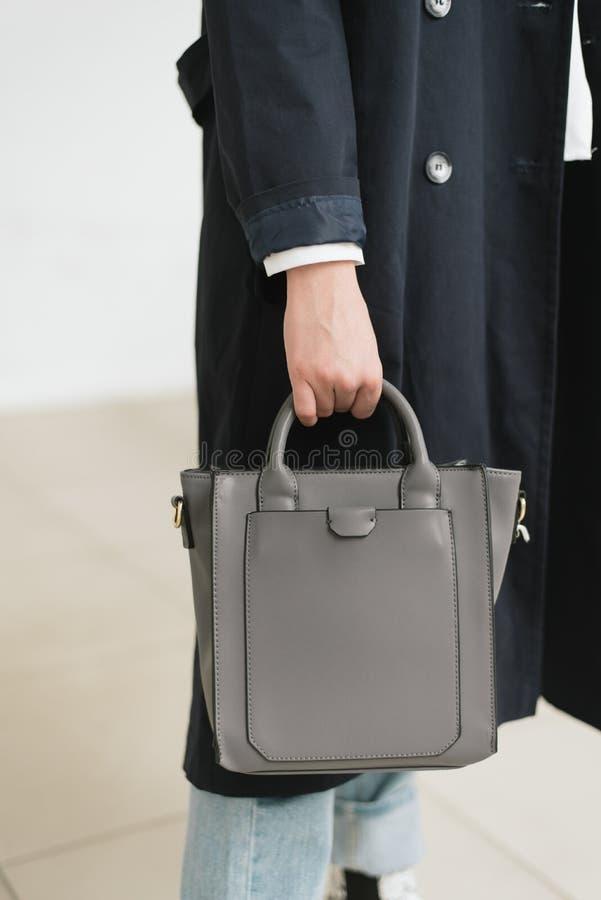 一个女孩的垂直的照片一个青灰色袋子的在手上 免版税库存图片