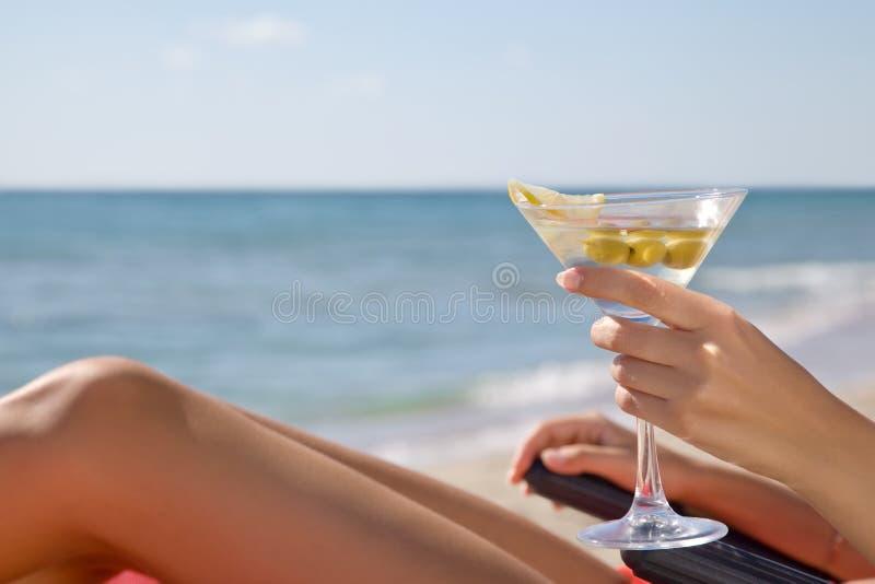 一个女孩的手有一个鸡尾酒的在海滩 免版税库存照片