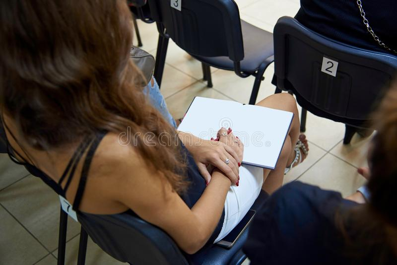 一个女孩的手有一支笔的在一个空的笔记薄 库存图片