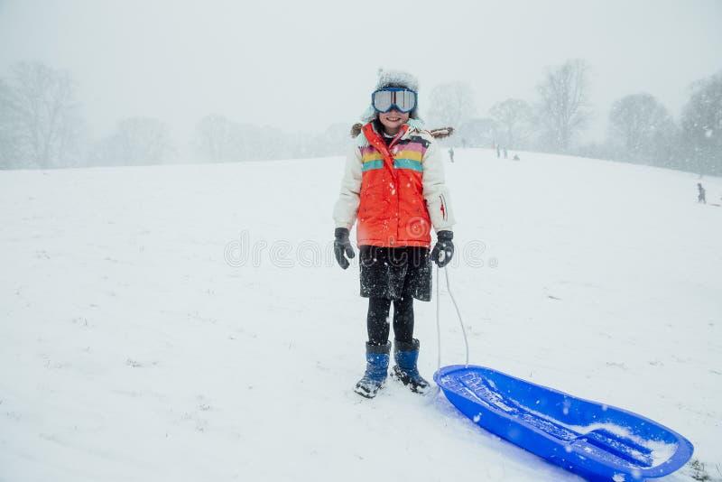 一个女孩的斯诺伊画象有雪撬的 免版税库存照片