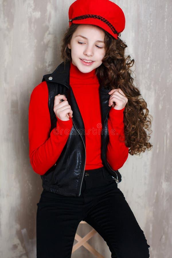 一个女孩的时髦的画象一个红色盖帽的在灰色背景在演播室 库存图片