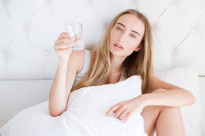 一个女孩的正面图用被弄乱的头发举行玻璃水,遭受的头痛在家坐床在客厅,宿酒 免版税库存图片