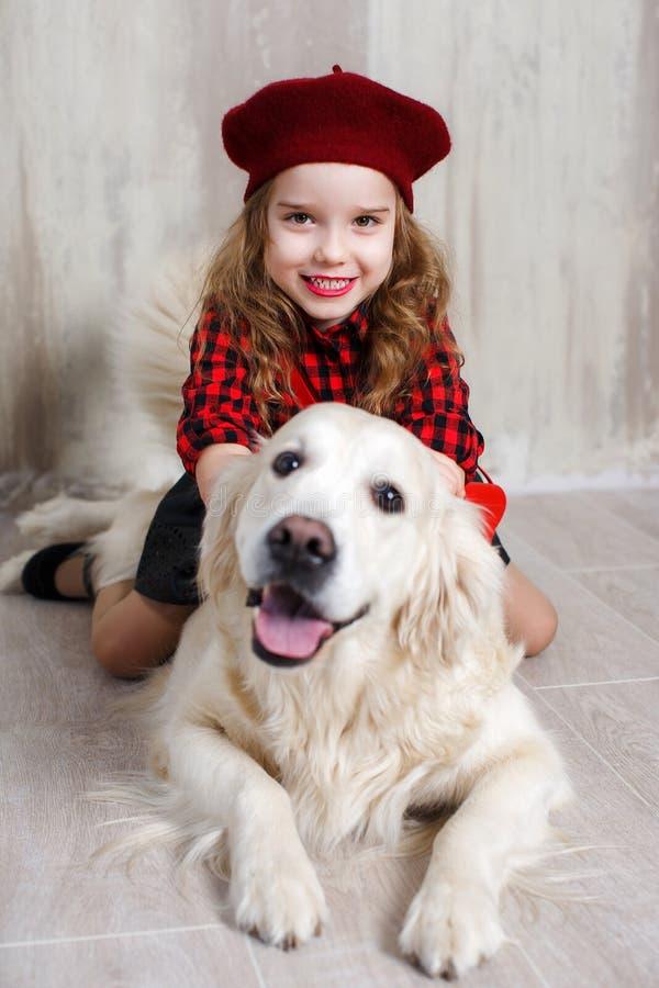 一个女孩的演播室画象有一条狗的在灰色背景 免版税库存图片