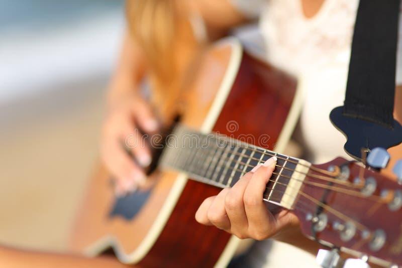 一个女孩的特写镜头弹经典吉他的海滩的 免版税库存照片