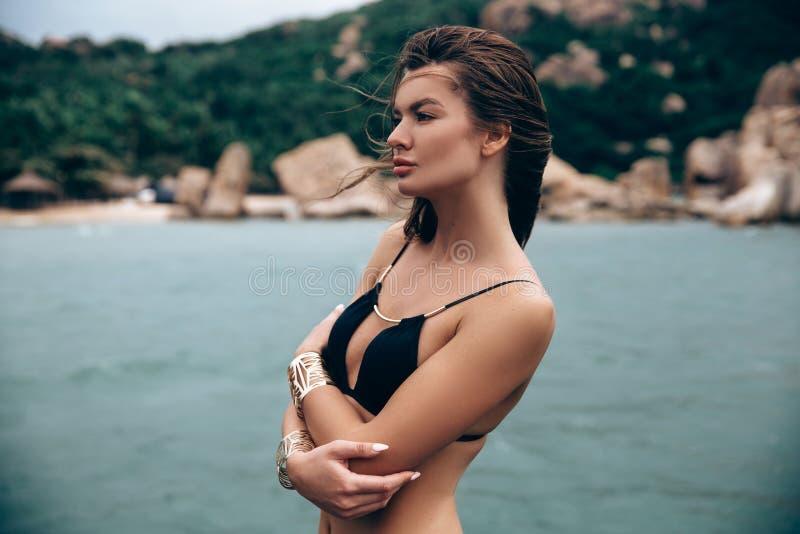 一个女孩的特写镜头游泳衣的在海滩单独站立,轻轻地拥抱与她的胳膊 图库摄影