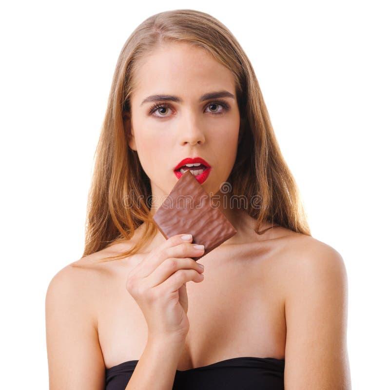 一个女孩的特写镜头,金发碧眼的女人,有巧克力片断的在白色背景隔绝的她的手上 免版税库存照片