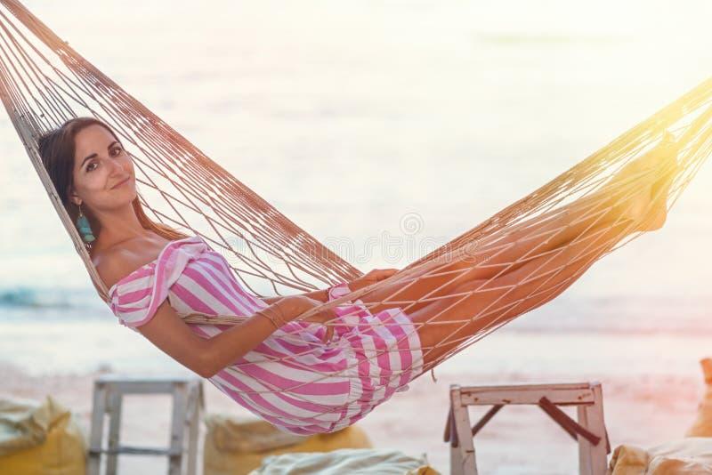 一个女孩的画象一个吊床的反对日落的海 库存照片
