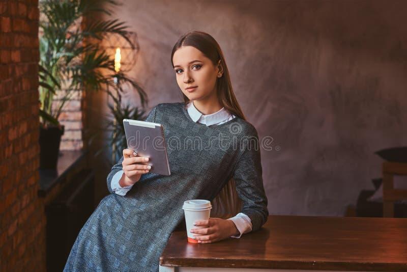 一个女孩的画象在一件典雅的灰色礼服举行穿戴了每杯子外带的咖啡并且拿着片剂,当时 免版税库存图片