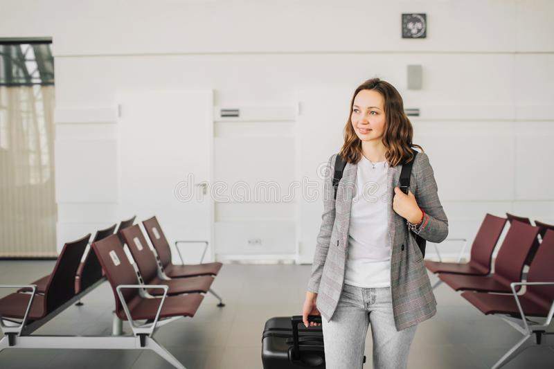 一个女孩的画象在机场,走与她的行李 免版税图库摄影