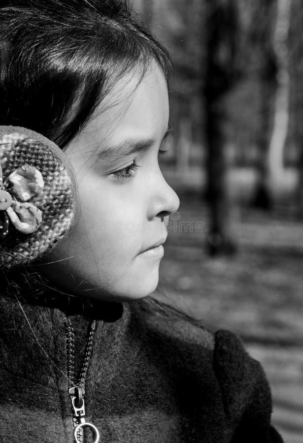 一个女孩的画象外形的在看温暖的耳机  免版税图库摄影