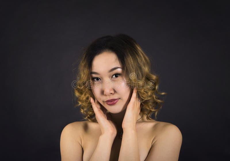 一个女孩的画象有光秃的肩膀的,与头发和构成在黑暗的背景 免版税库存照片